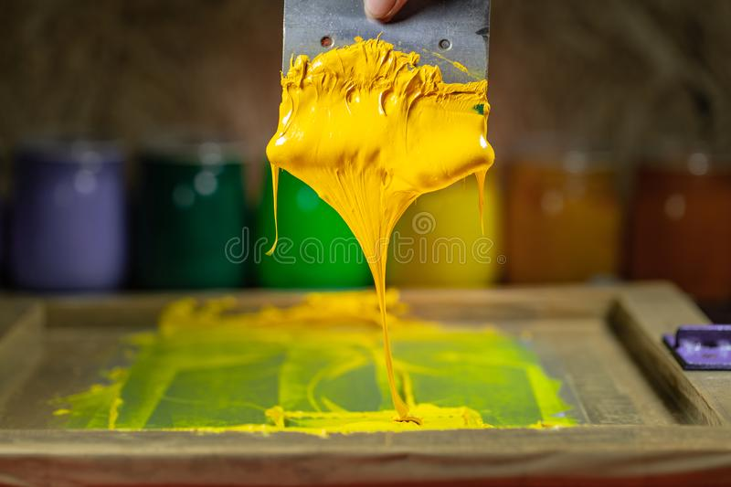 Yellow color dripping from hand screen printing. During printing tee shirt in tee shirt factory stock photography