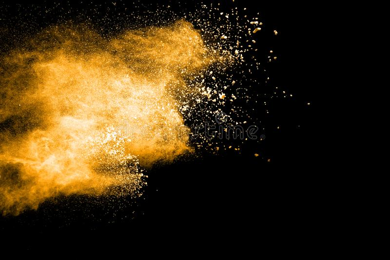Yellow Color powder explosion on black background stock image