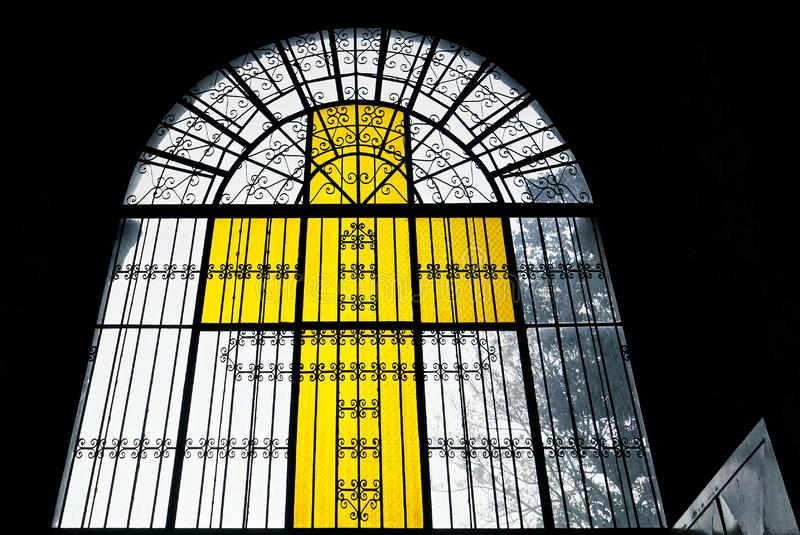 Yellow colored stained glass church window in cross form stock photos