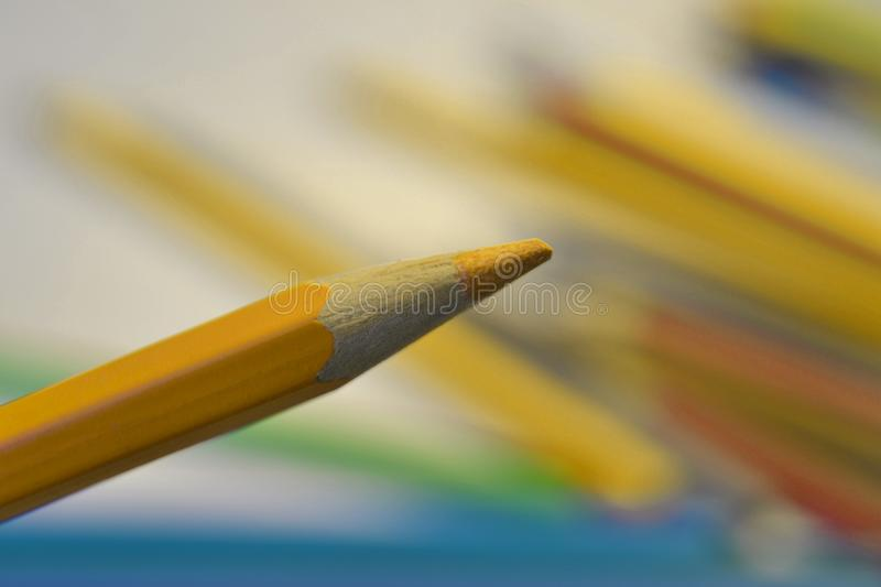 Yellow coloured pencil. On colourful background stock images