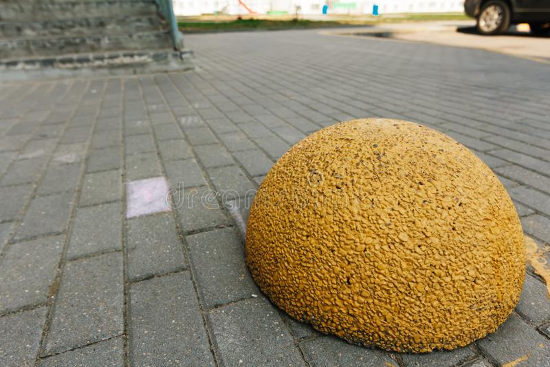 Yellow concrete hemisphere prohibiting parking barrier. Concrete limiter on road from granite pavers.  stock images