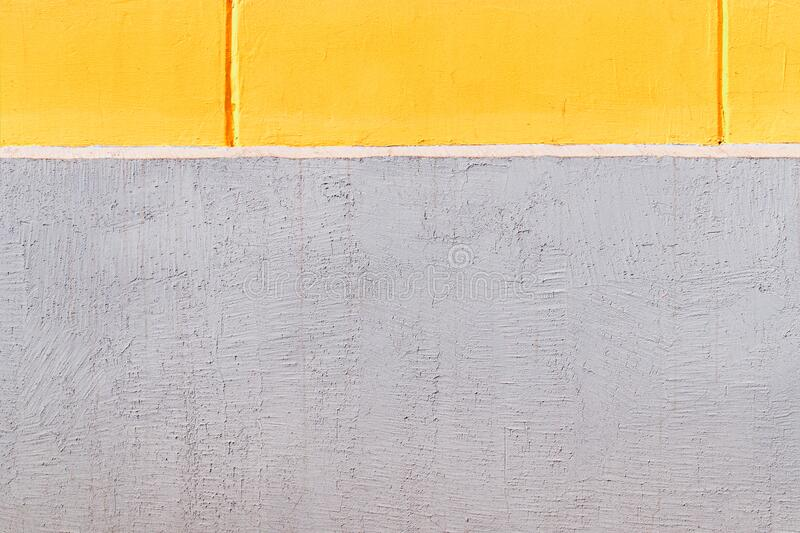 Yellow concrete wall and grey plinth as texture or background. The geometric style. The plastered surface. close up. Yellow concrete wall and grey plinth as stock image