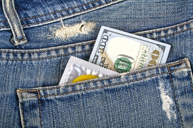 Yellow condom and one hundred dollars in a blue jeans pocket stock image