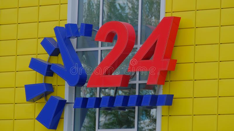 Yellow convenience store with a blue clock and big red numbers 24 hour service. Yellow convenience store with a blue clock and big red numbers 24 Daily service stock photo