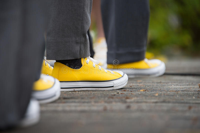 Yellow converse sneakers with grey slacks at a wedding stock image