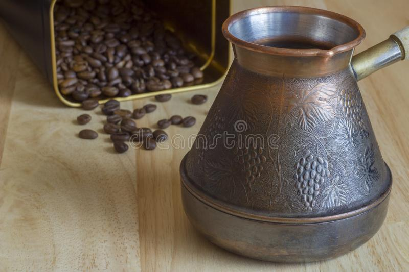 Yellow copper turk coffee maker on a blurred background of the wooden surface of the table with roasted brown coffee beans royalty free stock photos