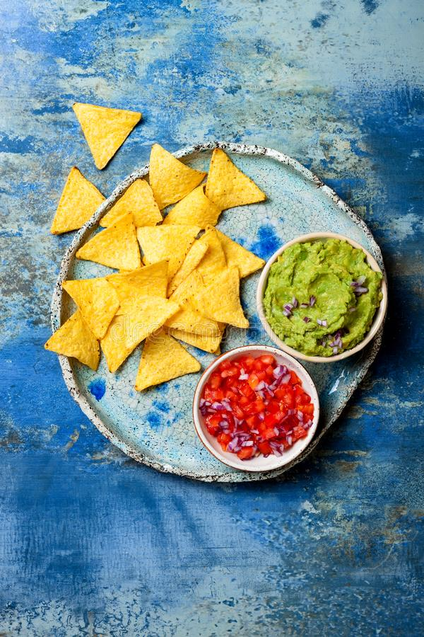 Yellow corn nachos chips with guacamole dip and tomato salsa over blue plate on blue stone background stock photography