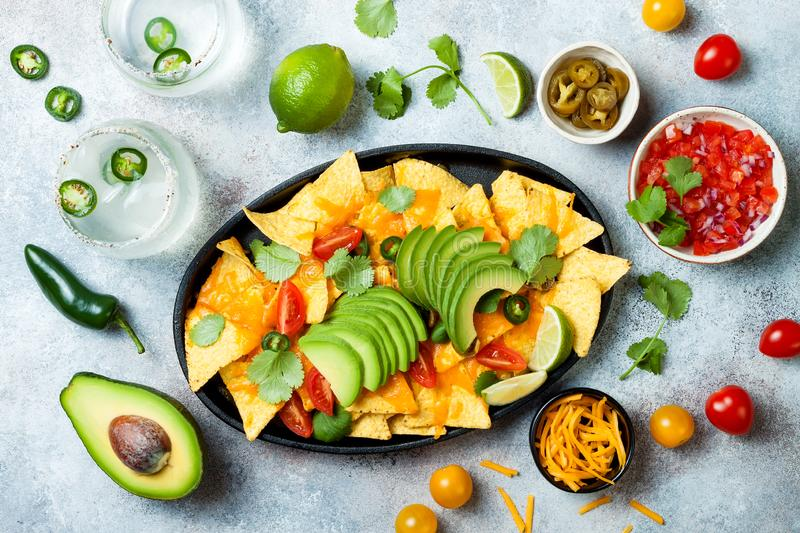 Yellow corn nachos chips with melted cheese sauce, avocado, jalapeno, cilantro leaves, tomato salsa and spicy iced margarita royalty free stock photography