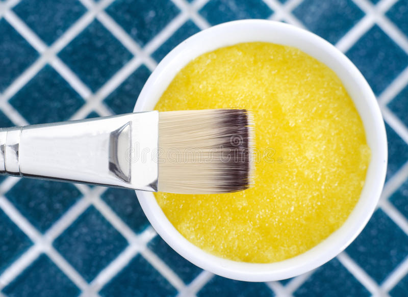 Yellow cosmetic mask (scrub) in a bowl royalty free stock image