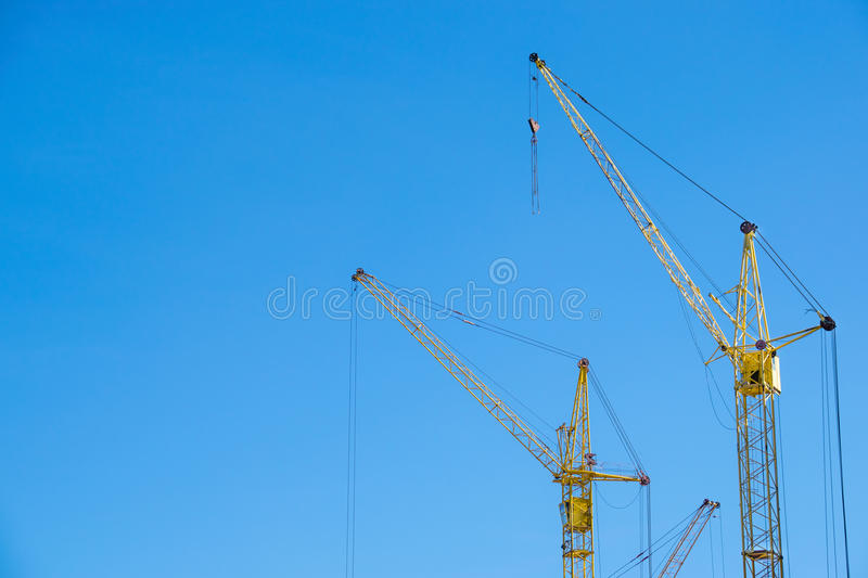 The yellow cranes at the construction site against the blue sky royalty free stock photos