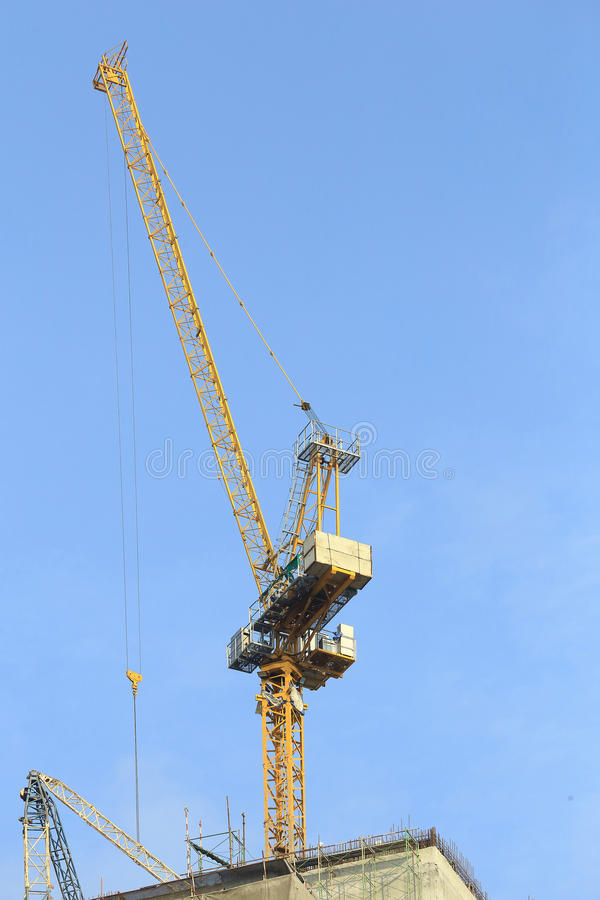 Yellow cranes in construction site with blue sky. stock photo