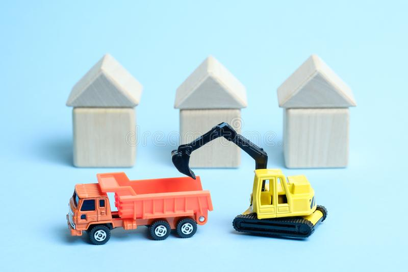 A yellow crawler excavator loads an orange dump truck against the background of houses built from wooden children`s royalty free stock photo