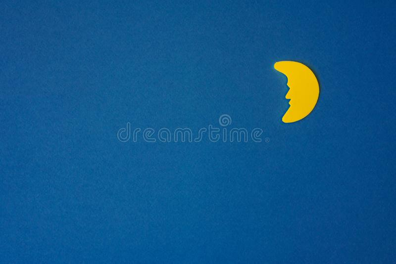 Yellow Crescent moon against blue night sky. Application paper on the right. Copy space royalty free stock image