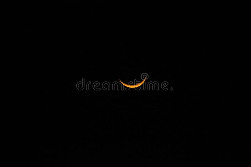 Yellow crescent moon in a starless sky. Sliver of a crescent moon surrounded by the dark abyss of night as seen from earth stock photography
