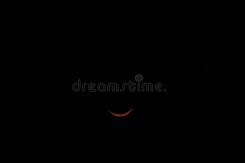 Yellow crescent moon in a starless sky. Sliver of a crescent moon surrounded by the dark abyss of night as seen from earth royalty free stock photo