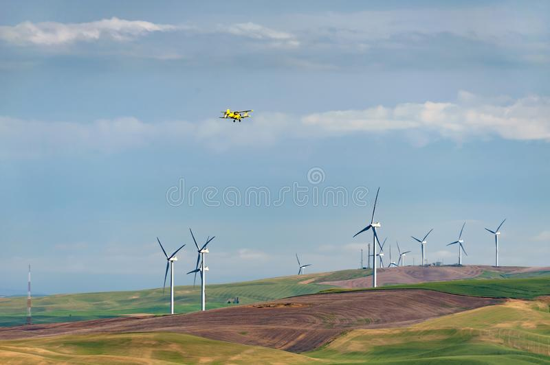Yellow Crop Duster Flying Over a Wind Farm in Eastern Washington. stock image