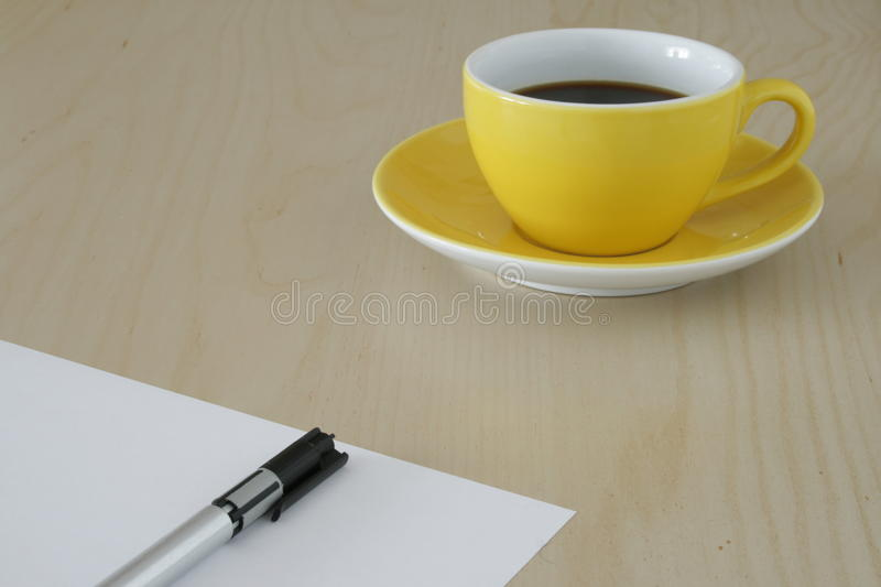 Yellow cup of coffee and a pen on paper. A cup of coffee besides a piece of paper with a pen on it symbolized a break from work or taking time for indepth stock photos