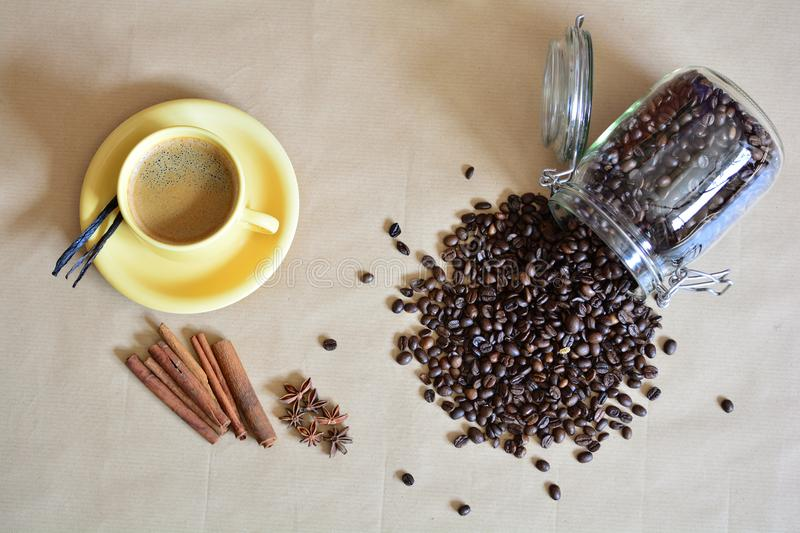 Cup of coffee with anise, vanilla and cinnamon sticks plus some spilled coffee beans royalty free stock photos