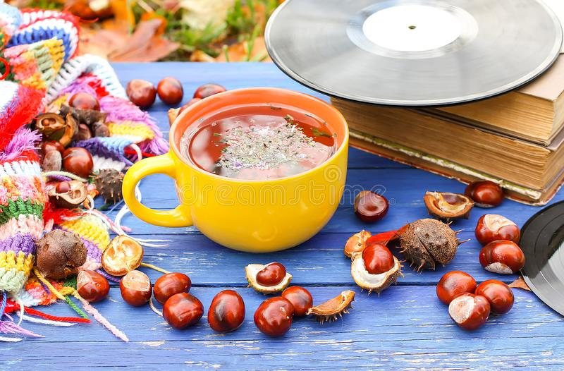 Yellow cup of herbal tea and vintage vinyl records on aged wooden background with fall autumn leaves and chestnuts. Yellow ceramic cup of herbal tea and vintage royalty free stock photo