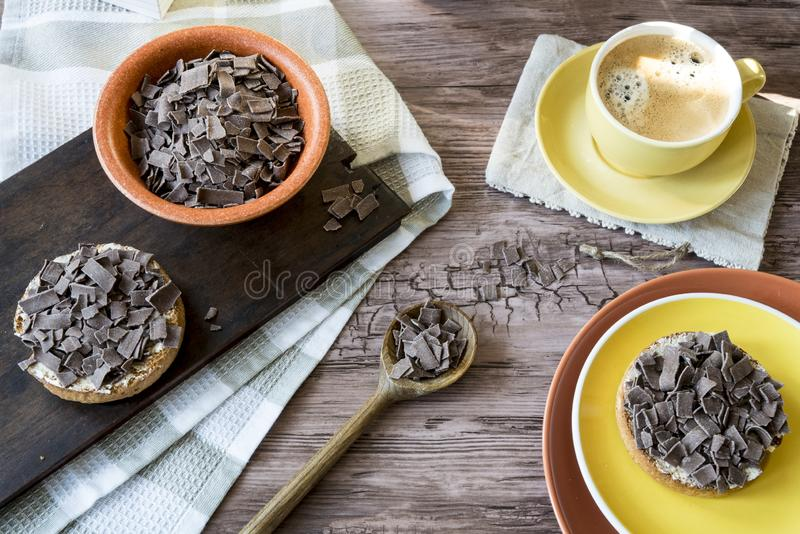 Dutch breakfast with rusk and chocolate hail, flakes and yellow mug of coffee. Yellow cup and saucer with coffee, plate and orange bowl with Dutch chocolate royalty free stock photography