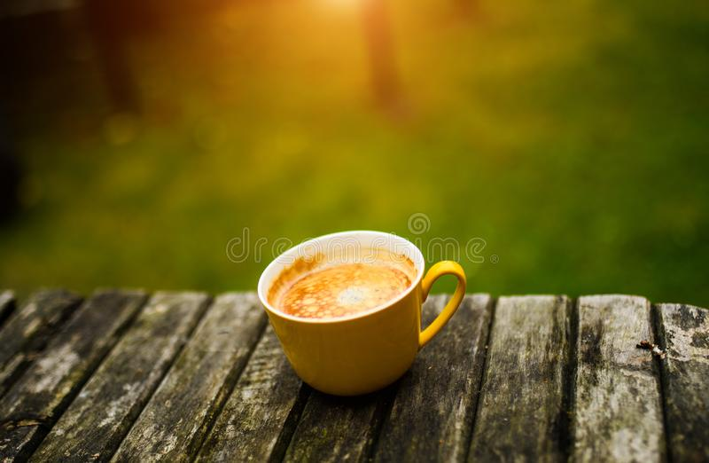 A yellow cup of tasty coffee, on rustic wooden table background royalty free stock images