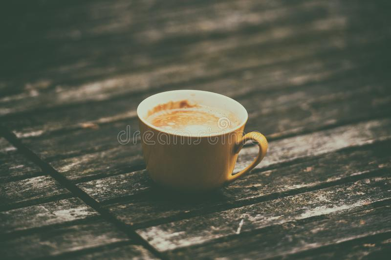 A yellow cup of tasty coffee, on rustic wooden table background stock images