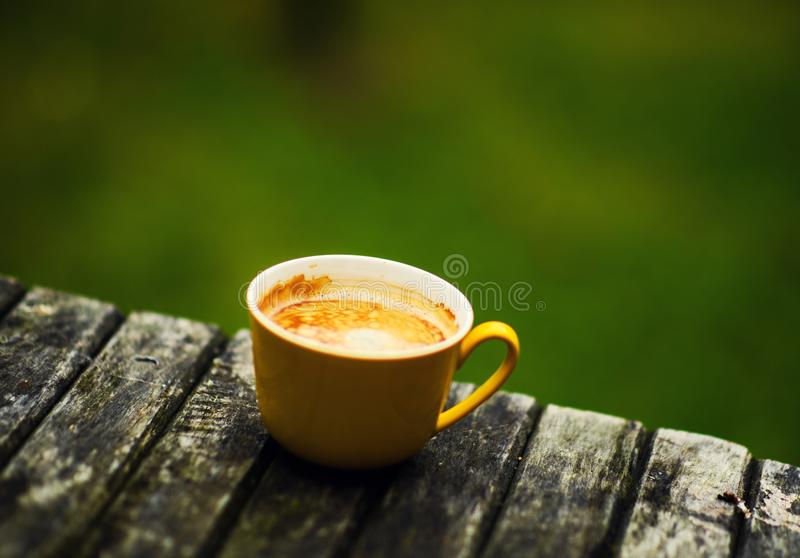 A yellow cup of tasty coffee, on rustic wooden table background stock image