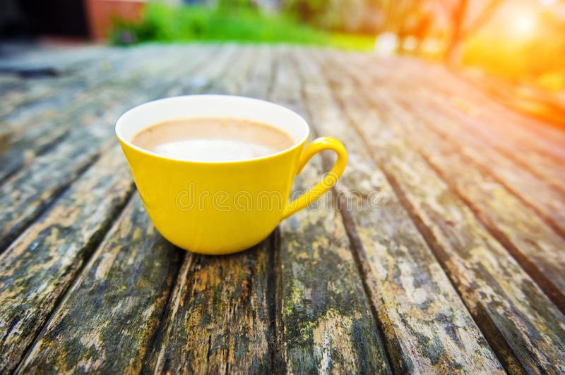 A yellow cup of tasty coffee, on rustic wooden table background. Spring time stock images