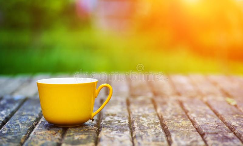 A yellow cup of tasty coffee, on rustic wooden table background. Spring time royalty free stock photos