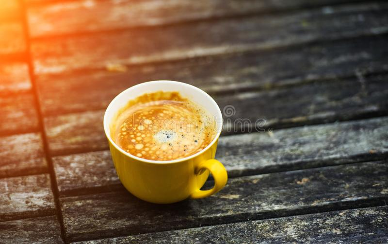 A yellow cup of tasty coffee, on rustic wooden table background. Summer time stock image