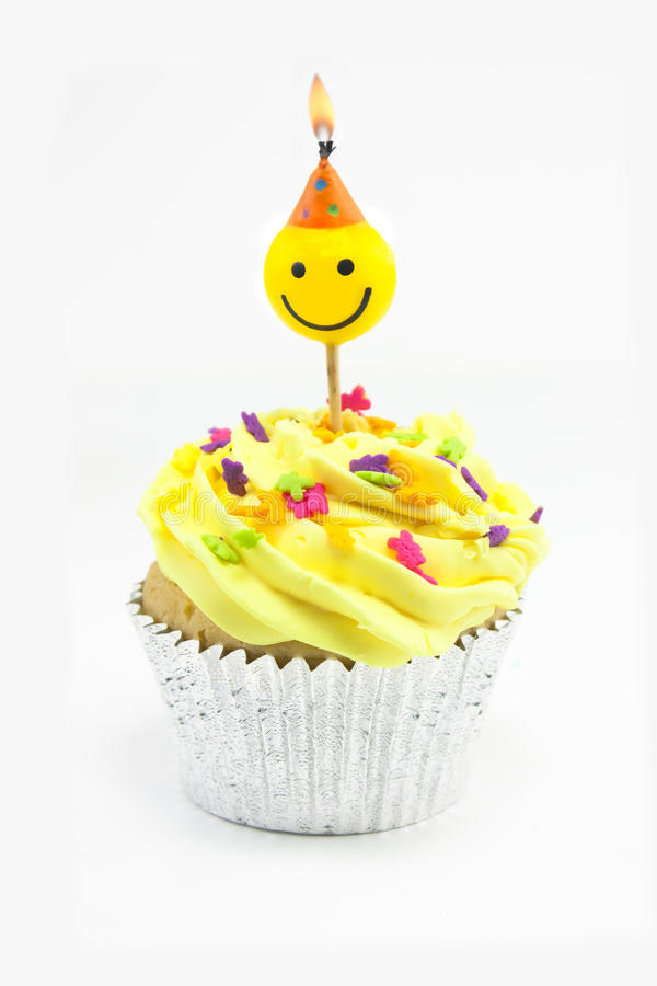 Yellow cupcake and smiley candle royalty free stock photo