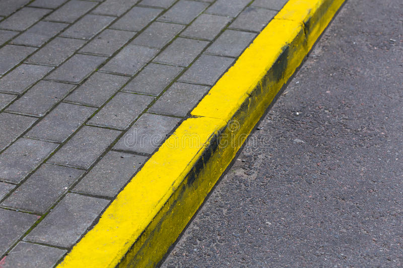 Yellow curb line on the road. Yellow kerb line on the asphalt proad royalty free stock photos