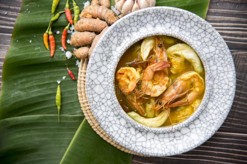 Yellow curry  shrimp, thai food and vegetable in white dish / selective focus and top view image,Sour soup made of Tamarind Paste. Or Turmeric,Is a food that is stock photos