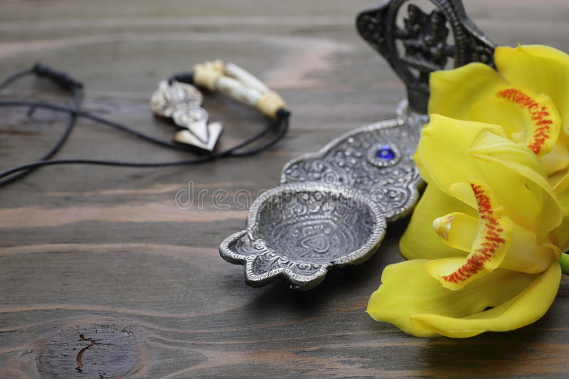 Yellow Cymbidium with incense burner and necklace stock photography