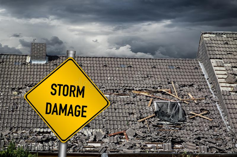 Yellow damage warning sign in front of storm damaged roof of house. Yellow damage warning sign in front of roof of house damaged by heavy hurricane tornado storm stock photo