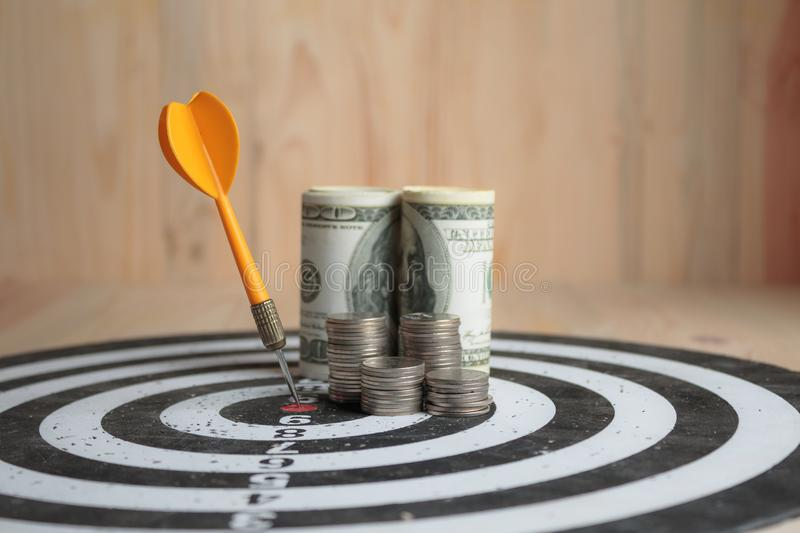 Yellow dart arrow hit the center target of dartboard and money c. Oin metaphor marketing or saving money concept, on wood background stock photography