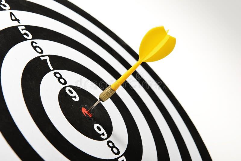 Yellow dart hitting target center royalty free stock images