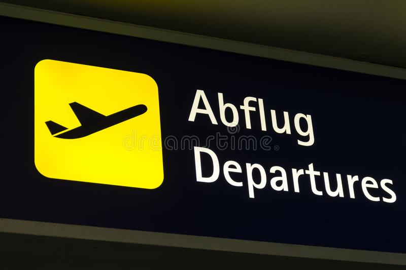 Yellow departures sign in German and English. Close up stock photography