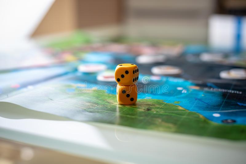 Yellow dice game on the blue field of fantasy game. Luck and excitement. Board games strategy stock photography