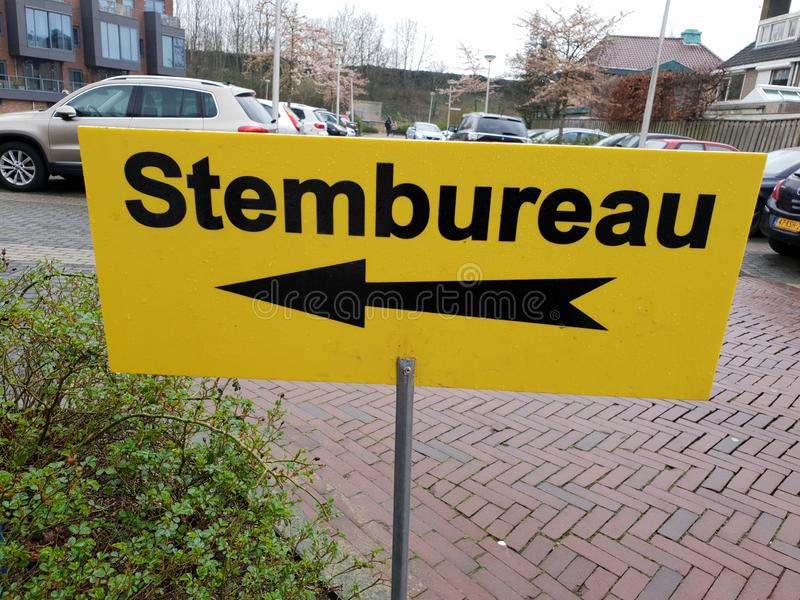 Yellow direction sign to polling station named stembureau in dutch for elections of the regional parlement in the Netherlands. stock photography
