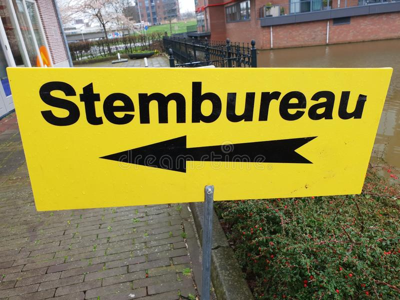 Yellow direction sign to polling station named stembureau in dutch for elections of the regional parlement in the Netherlands. stock photo