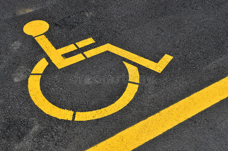 Yellow disabled people parking sign. Parking lot with yellow painted disabled people sign on grey asphalt floor stock images