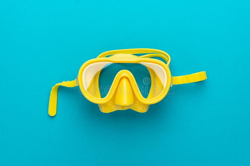 Yellow diving mask over blue background with central composition stock photo