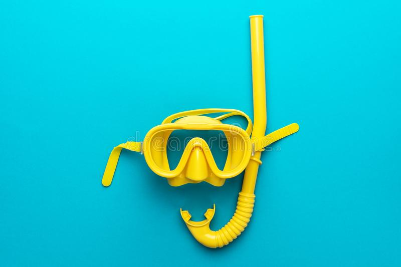 Yellow diving mask and snorkel over blue background with central composition stock photos
