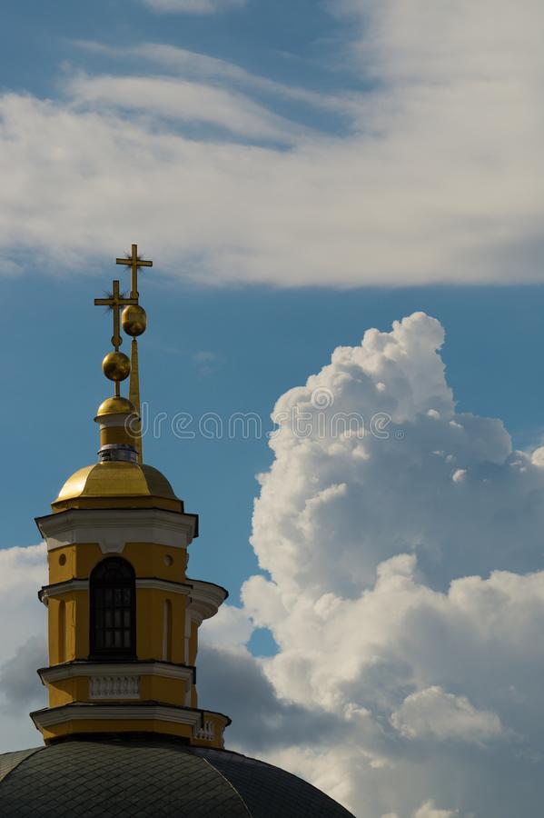 A yellow dome of a christian church against a blue sky. With invasive clouds royalty free stock image
