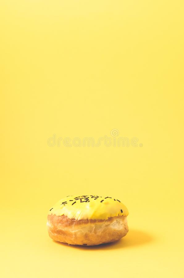 Yellow donut isolated on yellow background/Donut in yellow glaze decorated with dark chocolate sticks on yellow background with. Copy space, pink, berliner royalty free stock image