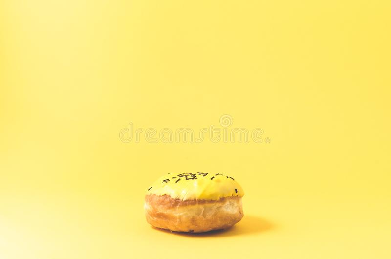 Yellow donut isolated on yellow background/Donut in yellow glaze decorated with dark chocolate sticks on yellow background. Selective focus stock photos