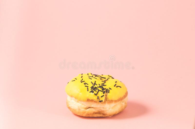 Yellow donut isolated on pink background/Donut in yellow glaze decorated with dark chocolate sticks on pink background. Selective. Focus, berliner, icing royalty free stock image