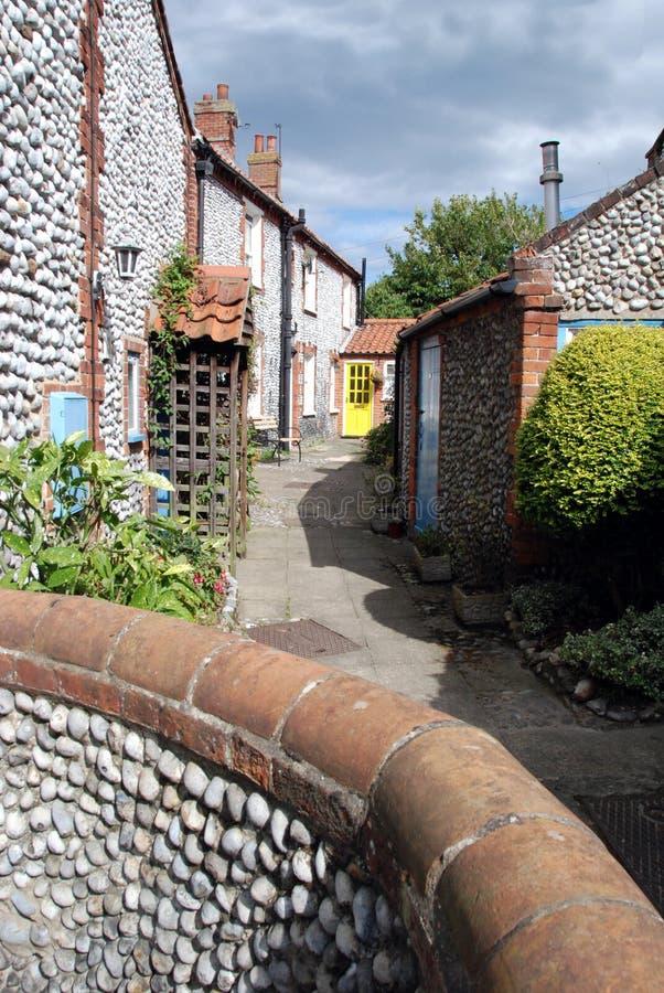 Yellow door. Sunlit yellow door at the end of an alleyway in a village in Norfolk, England stock photo