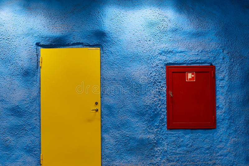 Yellow door on blue wall and red fire shield. Yellow door on blue wall with shadows and lights and red fire shield stock photos